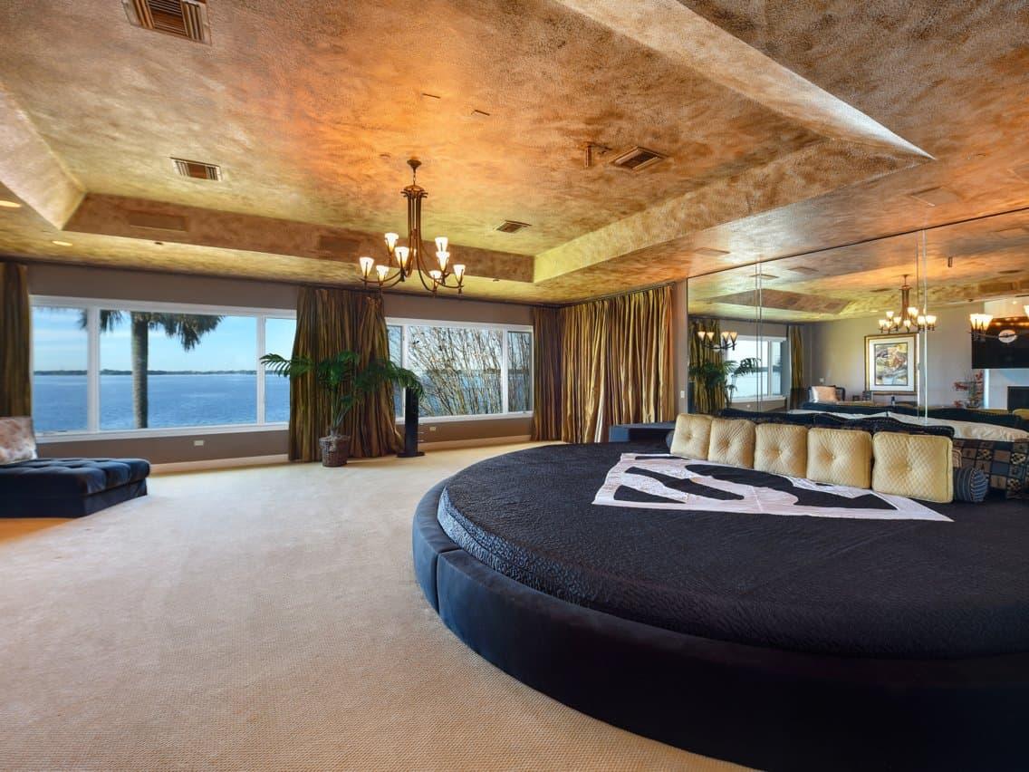 Phòng ngủ chính có tường, gương, trần nhà dát vàng và view mặt hồ sang chảnh