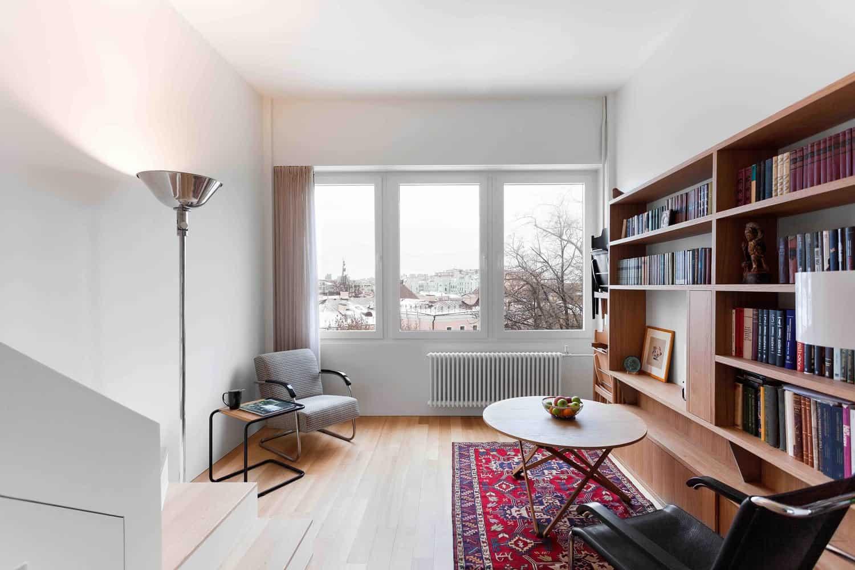 Phòng khách của căn hộ với góc làm việc, giá sách lớn và một ô cửa sổ lớn mang đến tầm nhìn tuyệt đẹp ra bên ngoài.