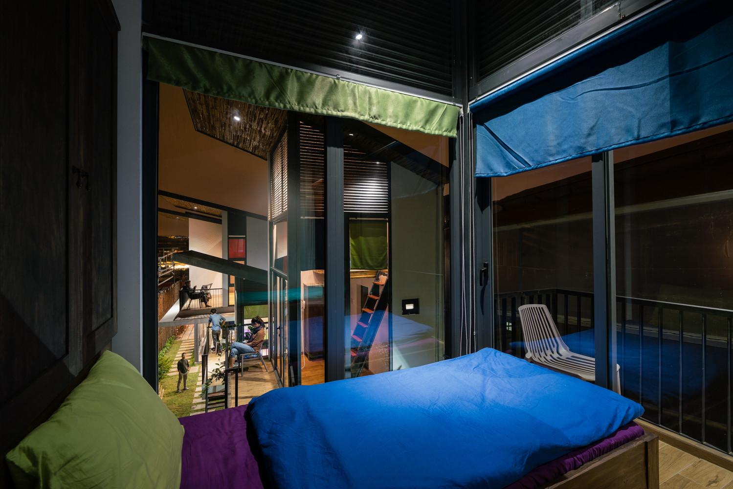 Một phòng trong homestay được thiết kế đơn giản với chăn ga, rèm phủ được tận dụng từ vải tái chế