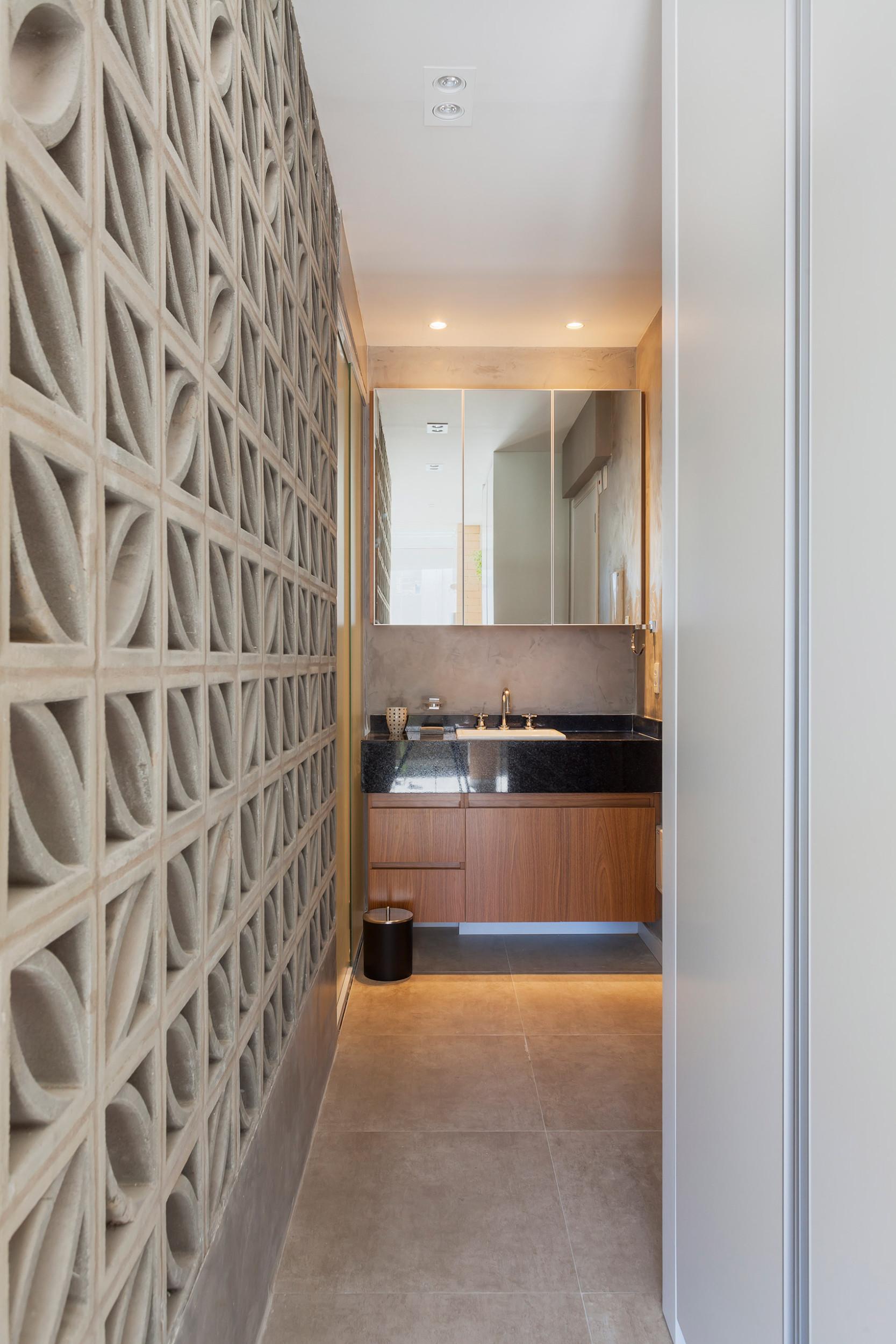 Lối dẫn vào phòng tắm. Bên cạnh lối đi là chiếc tủ cao kịch trần và bức tường gạch lỗ hoạ tiết