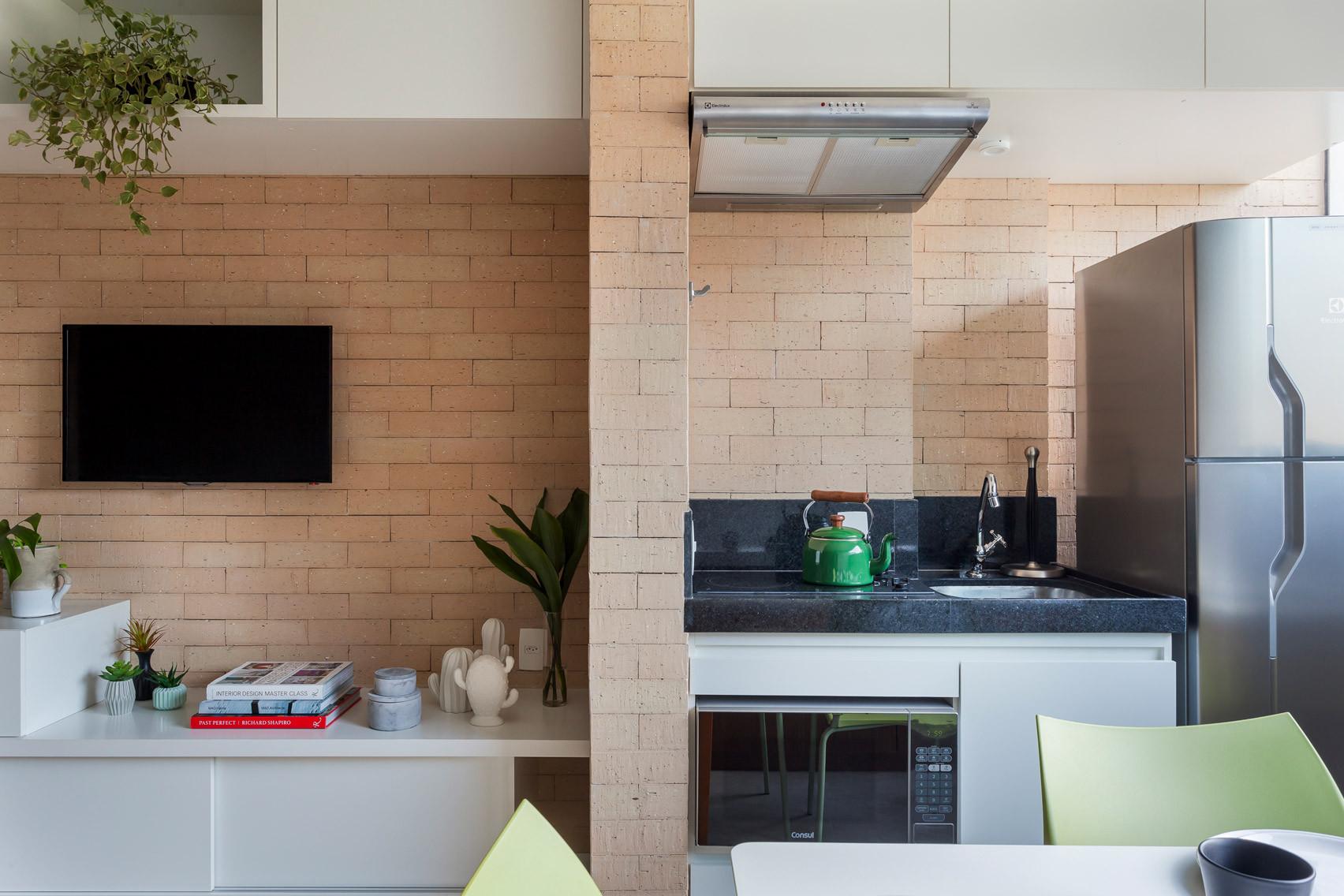 Khu vực bếp được ngăn cách với kệ trang trí phòng khách bằng một bức tường gạch dày.