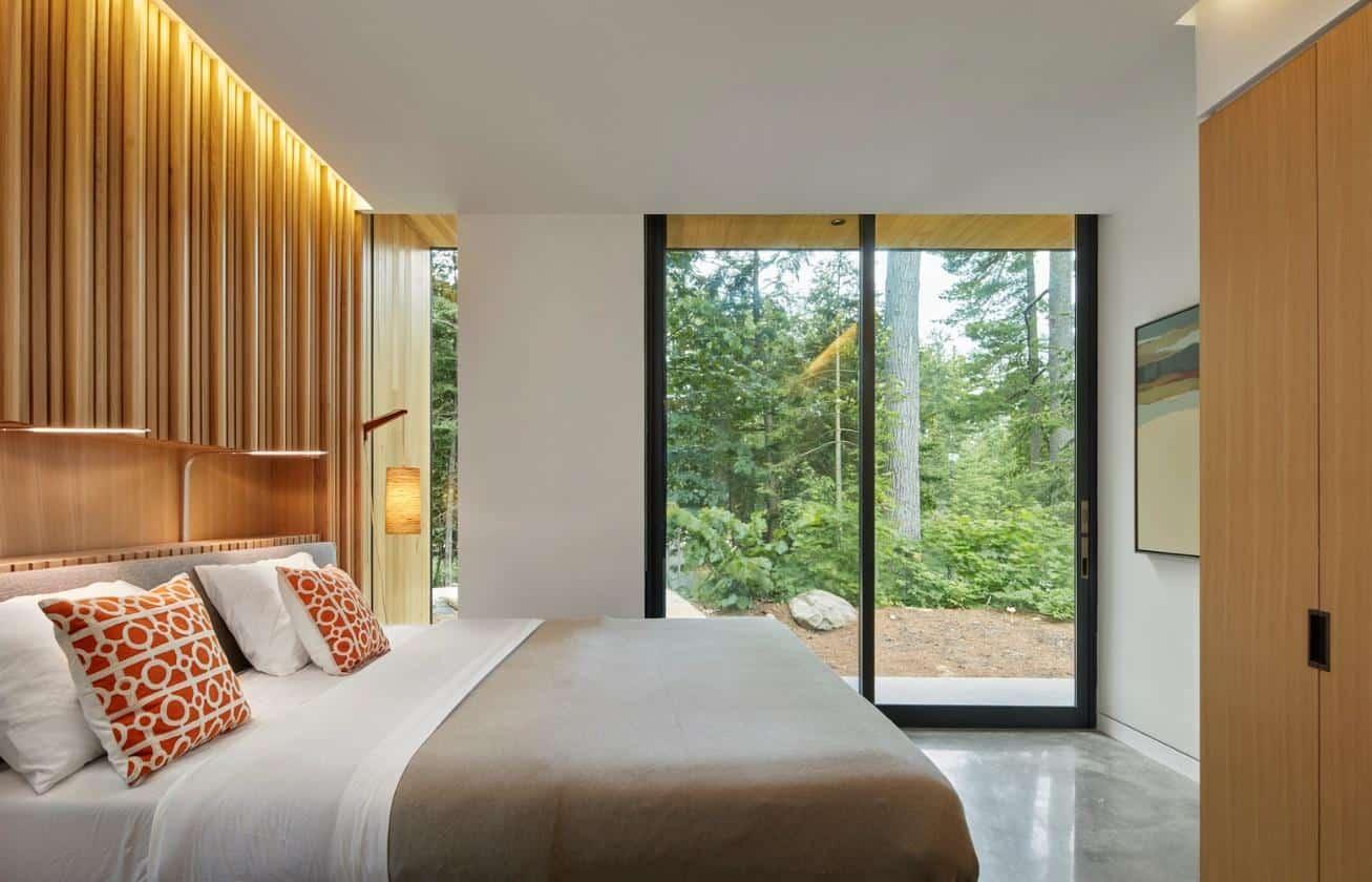 Ngay cả phòng ngủ cũng có cửa kính hướng ra ngoài, đón ảnh sáng mặt trời và ngắm nhìn cảnh sắc rừng thông cổ thụ. Có thể thấy thiết kế tường kính, cửa kính được tận dụng triệt để trong thiết kế của căn nhà này.