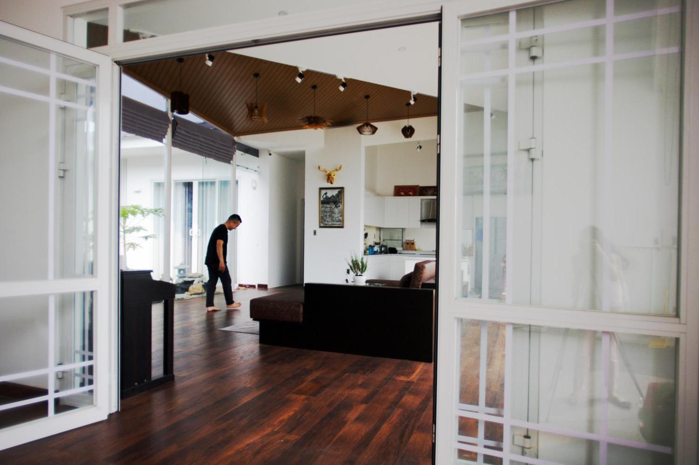 Bài trí trong nhà đơn giản với sàn gỗ, nội thất gỗ và cửa kính.