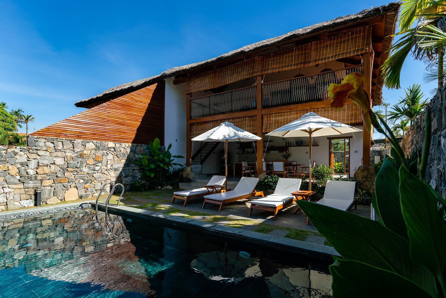 Bên ngoài nhà là bể bơi. 2 căn biệt thự ngăn cách nhau bởi bức tường gạch cao.
